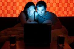 Pares en un sofá que mira una película Imágenes de archivo libres de regalías