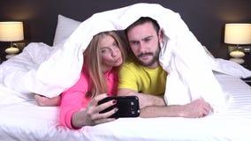 Pares en una cama cómoda que toma un selfie almacen de metraje de vídeo