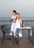 Pares en una cena romántica en la playa Imágenes de archivo libres de regalías
