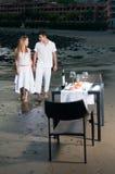 Pares en una cena romántica en la playa Imagen de archivo