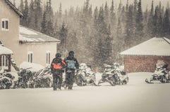 Pares en una moto de nieve en el bosque Foto de archivo