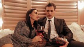 Pares en vino tinto y alegrías de la bebida de la pasión por Año Nuevo en un hotel en una cámara lenta de la cama metrajes