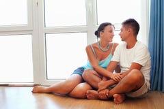 Pares enamorados que se sientan en suelo cerca de ventana Imagenes de archivo