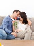 Pares enamorados que se sientan junto en el sofá Fotografía de archivo