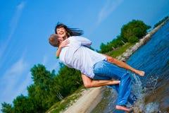 Pares Enamored que abraçam na praia ensolarada foto de stock