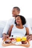 Pares Enamored que comem o pequeno almoço em sua cama fotografia de stock royalty free