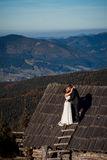 Pares encantadores de la boda que se besan en el tejado de la casa de campo Fondo asombroso del paisaje de la montaña honeymoon Foto de archivo libre de regalías