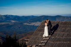 Pares encantadores de la boda que se besan en el tejado de la casa de campo Fondo asombroso del paisaje de la montaña honeymoon imagen de archivo