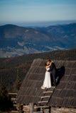 Pares encantadores do casamento que beijam no telhado da casa de campo Fundo surpreendente da paisagem da montanha honeymoon Foto de Stock Royalty Free