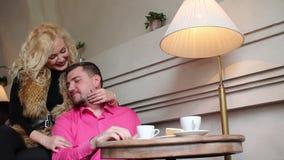 Pares encantadores mulheres louras que afagam um mordente do ` s do indivíduo no café vídeos de arquivo