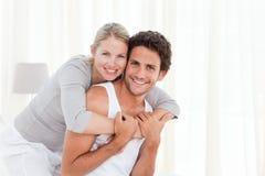 Pares encantadores que abraçam em sua cama foto de stock royalty free