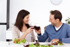 Pares encantadores que brindam vidros do vinho vermelho Imagem de Stock