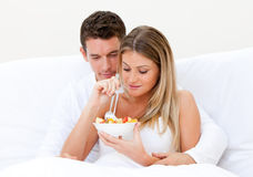 Pares encantadores que comem a salada de fruta na cama imagens de stock royalty free