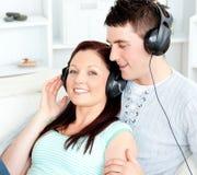 Pares encantadores que escuchan la música con los auriculares Imagenes de archivo