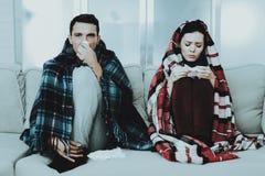 Pares enfermos que se sientan en el sofá en mantas a cuadros fotos de archivo