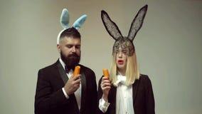 Pares engraçados felizes de easter com cenoura A família comemora a Páscoa Coelhos da Páscoa Pares com orelhas do coelho Easter e video estoque