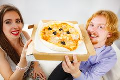 Pares engra?ados que comem a pizza imagem de stock royalty free