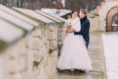 Pares enloved románticos del recién casado que abrazan feliz junto cerca de la pared vieja del castillo Imagenes de archivo