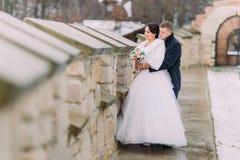 Pares enloved románticos del recién casado que abrazan junto cerca de la pared vieja del castillo Imágenes de archivo libres de regalías