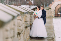 Pares enloved românticos do recém-casado que abraçam junto perto da parede velha do castelo Imagens de Stock Royalty Free