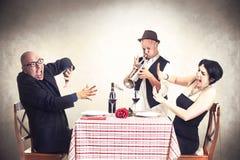 Pares enojados perturbados por un músico de la trompeta mientras que cenando Imágenes de archivo libres de regalías
