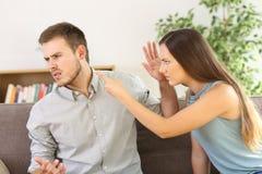 Pares enojados que discuten en un sofá en casa Foto de archivo libre de regalías