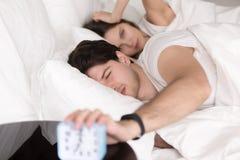 Pares enojados soñolientos en la cama que apaga el despertador Fotos de archivo