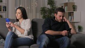 Pares enojados usando sus smartphones después de la discusión almacen de metraje de vídeo