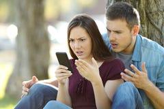 Pares enojados usando un teléfono elegante al aire libre Fotografía de archivo