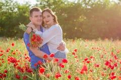 Pares entre el campo de la amapola que abraza y que sonríe Foto de archivo libre de regalías