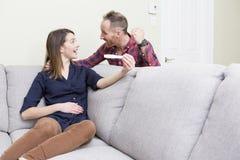 Pares entusiasmado felizes que fazem o teste de gravidez positivo e que comemoram Fotografia de Stock Royalty Free