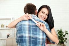 Pares entusiasmado felizes que fazem o teste de gravidez positivo e que comemoram Imagens de Stock