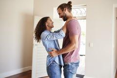 Pares entusiasmado que abraçam pela casa nova aberta de Front Door In Lounge Of imagem de stock