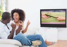 Pares entusiasmado que cheering e que olham esportes na televisão imagens de stock