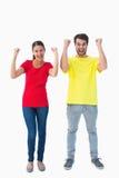 Pares entusiasmado que cheering em tshirts vermelhos e amarelos fotografia de stock