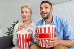 pares entusiasmados que comem a pipoca e que olham afastado fotografia de stock royalty free