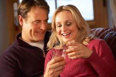 Pares envejecidos centro en el sofá con los vidrios de whisky Foto de archivo libre de regalías