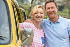 Pares envejecidos centro feliz del hombre y de la mujer con el campista Van Bus imagenes de archivo