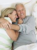 Pares envejecidos centro que abrazan en cama Foto de archivo libre de regalías