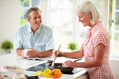 Pares envejecidos centro que cocinan la comida en cocina junto Foto de archivo libre de regalías