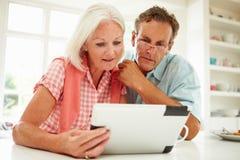Pares envejecidos centro que miran la tableta de Digitaces imagenes de archivo