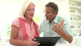 Pares envejecidos centro que miran la tableta de Digitaces que tiene discusión almacen de metraje de vídeo