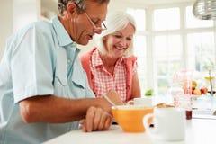 Pares envejecidos centro que miran la tableta de Digitaces sobre el desayuno foto de archivo libre de regalías