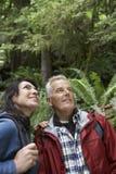 Pares envejecidos centro que miran para arriba en bosque Foto de archivo