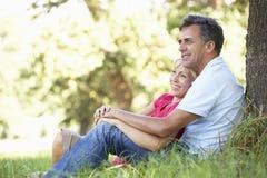 Pares envejecidos centro que se relajan en el campo que se inclina contra árbol Foto de archivo