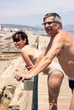 Pares envejecidos centro que se relajan en la playa Foto de archivo libre de regalías