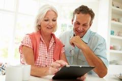 Pares envejecidos centro sonrientes que miran la tableta de Digitaces imágenes de archivo libres de regalías