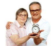 Pares envejecidos con el reloj de alarma en plam Imagenes de archivo