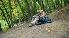 Pares envejecidos de amor alegres de los turistas que tienen una rotura en el bosque metrajes