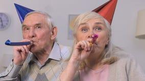 Pares envejecidos divertidos en los sombreros del partido que disfrutan de la celebración, divirtiéndose junto almacen de metraje de vídeo